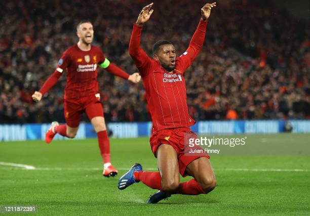 Georginio Wijnaldum of Liverpool celebrates with Jordan Henderson after scoring his team's first goal during the UEFA Champions League round of 16...