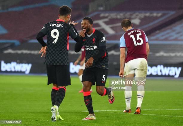Georginio Wijnaldum of Liverpool celebrates with team mate Roberto Firminho after scoring their side's third goal during the Premier League match...