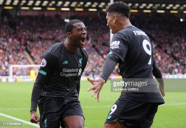 Georginio Wijnaldum of Liverpool celebrates with teammate Roberto Firmino after scoring his team's first goal during the Premier League match between...