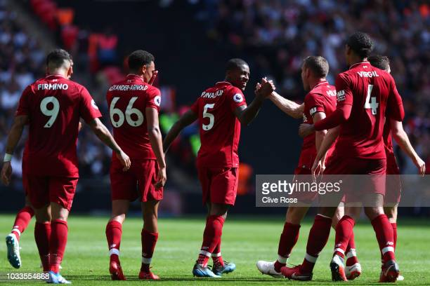 Georginio Wijnaldum of Liverpool celebrates with teammates after scoring his team's first goal during the Premier League match between Tottenham...