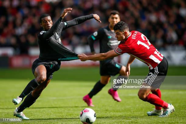 Georginio Wijnaldum of Liverpool has his shirt pulled by John Egan of Sheffield United during the Premier League match between Sheffield United and...