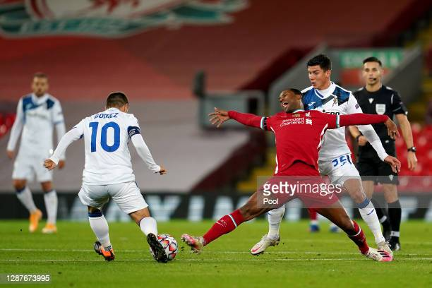 Georginio Wijnaldum of Liverpool is challenged by Alejandro Gomez and Matteo Pessina of Atalanta B.C. During the UEFA Champions League Group D stage...