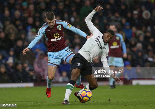 Georginio Wijnaldum of Liverpool is challenged by Johann Gudmundsson of Burnley during the Premier League match between Burnley and Liverpool at Turf...