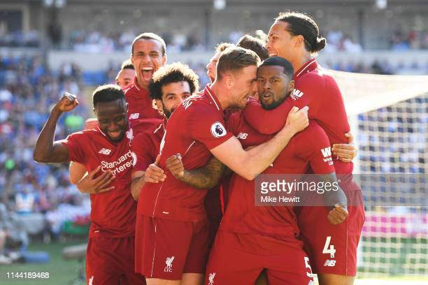 Georginio Wijnaldum of Liverpool is surrounded by team mates after scoring during the Premier League match between Cardiff City and Liverpool FC at...