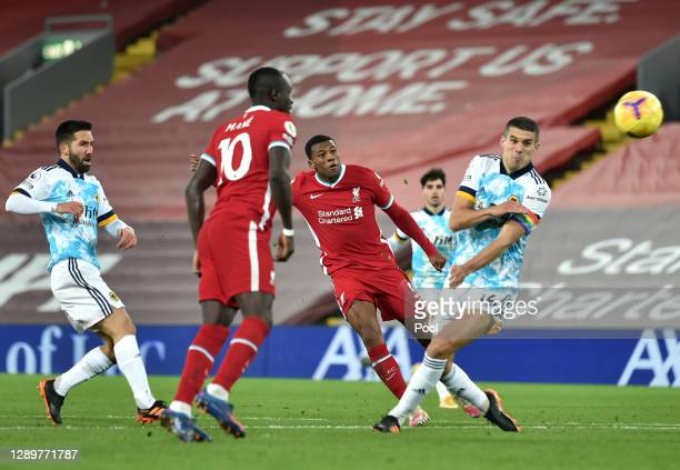 Georginio Wijnaldum of Liverpool scores their sides second goal whilst under pressure from Conor Coady of Wolverhampton Wanderers during the Premier...