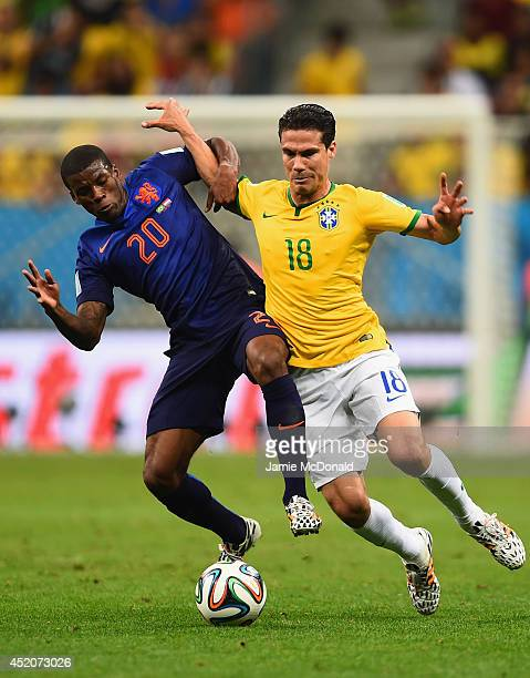 Georginio Wijnaldum of the Netherlands and Hernanes of Brazil compete for the ball during the 2014 FIFA World Cup Brazil Third Place Playoff match...