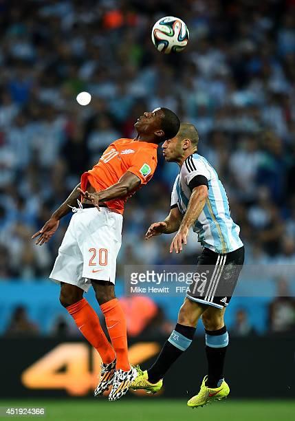 Georginio Wijnaldum of the Netherlands and Javier Mascherano of Argentina clash during the 2014 FIFA World Cup Brazil Semi Final match between...