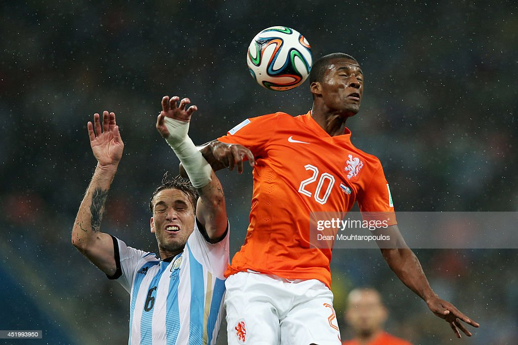 Georginio Wijnaldum (R) of the Netherlands competes for the header with Lucas Biglia of Argentina during the 2014 FIFA World Cup Brazil Semi Final match between Netherlands and Argentina at Arena de Sao Paulo on July 09, 2014 in Sao Paulo, Brazil.