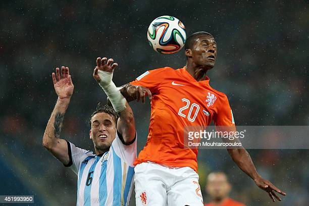 Georginio Wijnaldum of the Netherlands competes for the header with Lucas Biglia of Argentina during the 2014 FIFA World Cup Brazil Semi Final match...