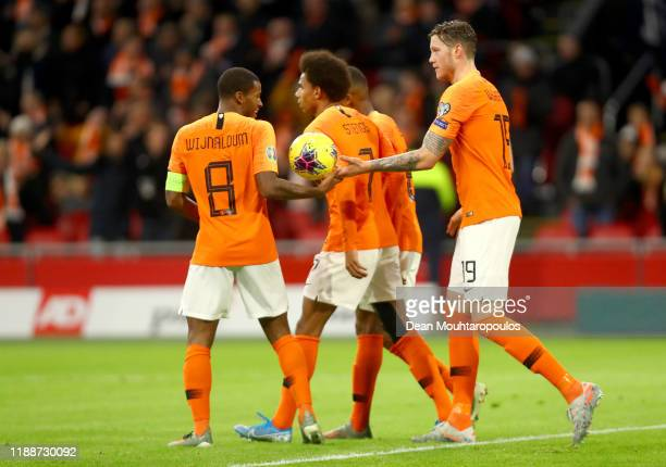 Georginio Wijnaldum of The Netherlands is handed by the ball by Wout Weghorst as he celebrates after scoring his hat trick and his sides fourth goal...