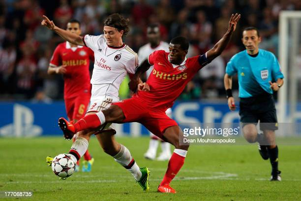 Georgino Wijnaldum of PSV and Riccardo Montolivo of AC Milan battle for the ball during the UEFA Champions League Playoff First Leg match between PSV...