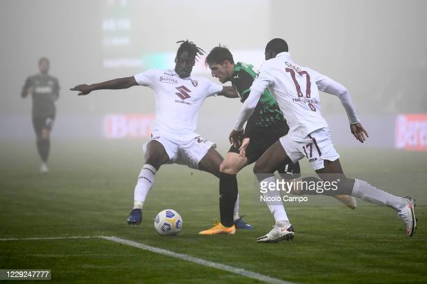 Georgios Kyriakopoulos of US Sassuolo is challenged by Soualiho Meite and Wilfried Singo of Torino FC during the Serie A football match between US...
