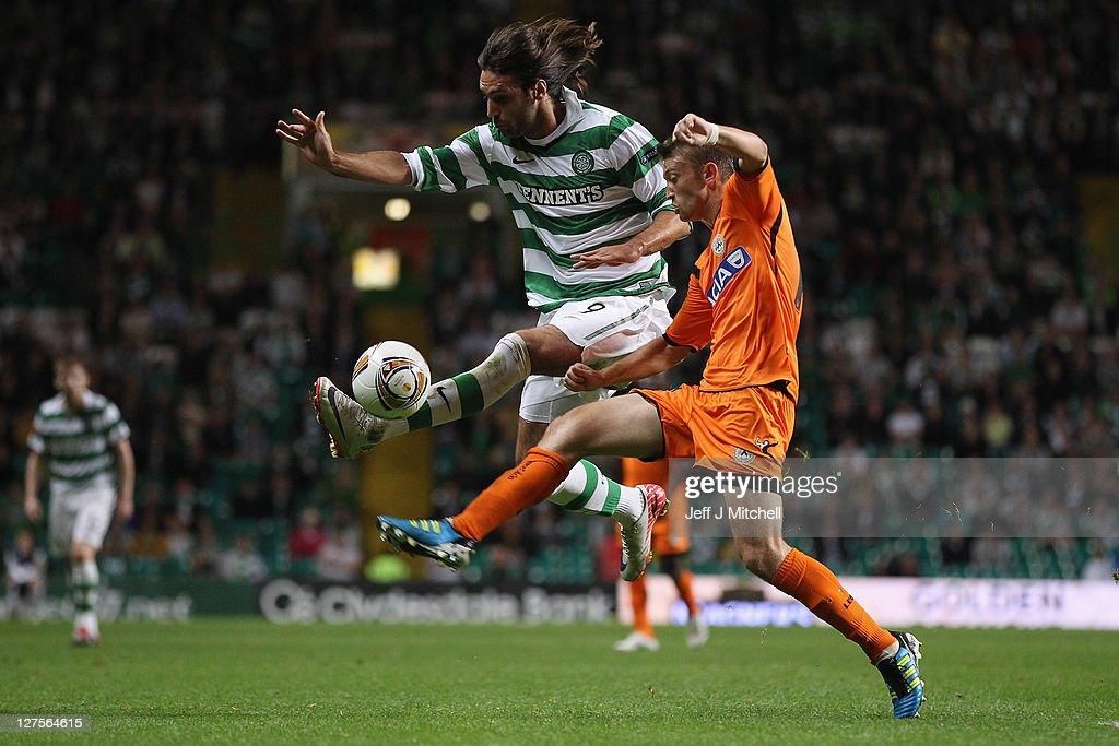 Georgios Samaras of Celtic tackles Cristian Battochio of Udinese during the Europa League Group I match between Celtic and Udinese at Celtic Park on September 29, 2011 in Glasgow, United Kingdom.