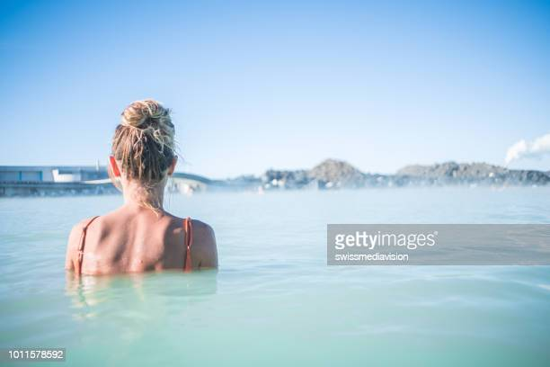 geothermal spa. woman relaxing in hot spring pool in iceland. girl enjoying bathing in a blue water lagoon icelandic tourist attraction. - iceland stock pictures, royalty-free photos & images