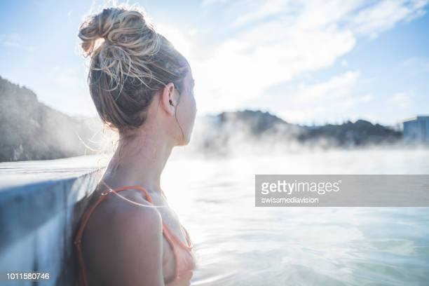 geothermal spa. woman relaxing in hot spring pool in iceland. girl enjoying bathing in a blue water lagoon icelandic tourist attraction. - hot spring stock pictures, royalty-free photos & images