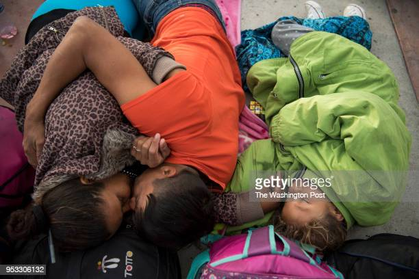 Geovany Aguirre lays with Iris Flores left and Meyli Flores right while they wait overnight in a fenced area at the San Ysidro border crossing to...
