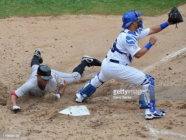 Geovany Soto of the Chicago Cubs can't make a tag on Angel Sanchez of the Houston Astros at home plate on July 23 2011 at Wrigley Field in Chicago...