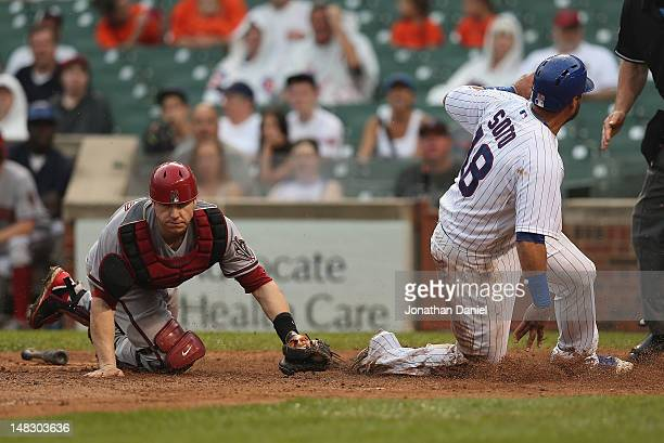 Geovany Soto of the Chicago Cubs scores a run on a squeeze play as Miguel Montero of the Arizona Diamondbacks misses the tag at Wrigley Field on July...