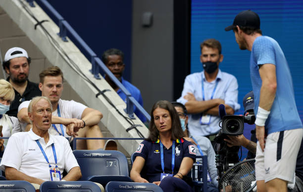 Former chair umpire Gerald Armstrong speaks with Andy Murray of United Kingdom against Stefanos Tsitsipas of Greece during their men's singles first...