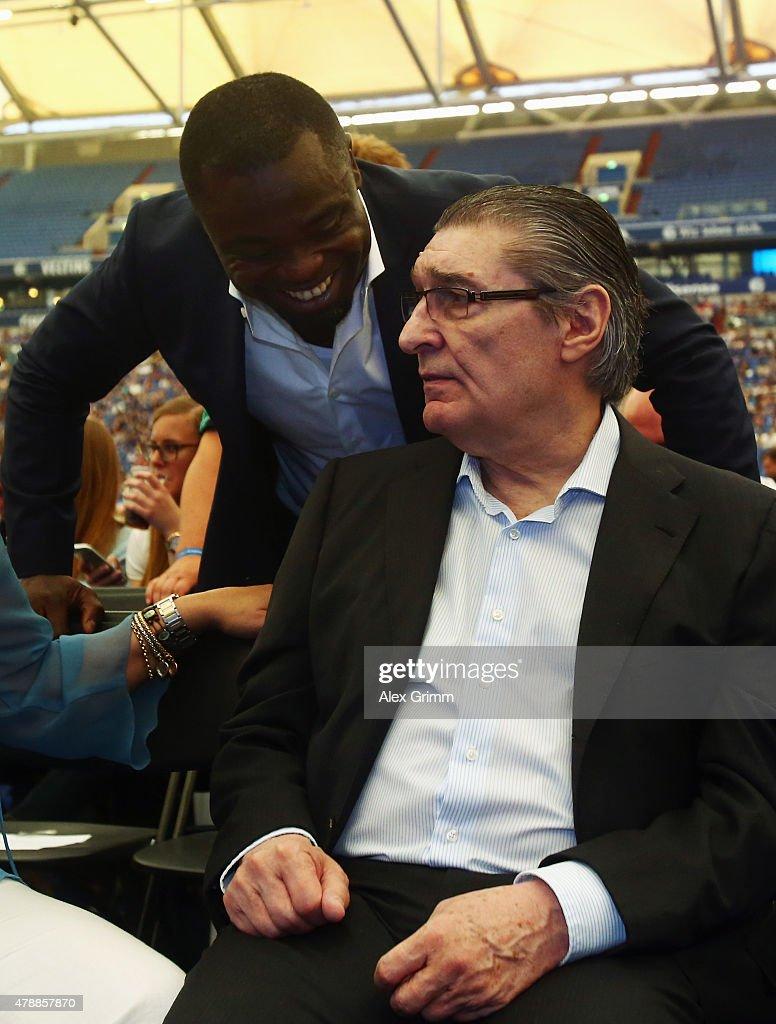 Gerald Asamoah, a former player, talks to former manager Rudi Assauer during the general assembly of FC Schalke 04 at Veltins-Arena on June 28, 2015 in Gelsenkirchen, Germany.