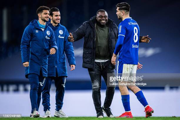 Gerald Asamoah congrats scorer Suat Serdar after the Bundesliga match between FC Schalke 04 and FC Augsburg at Veltins-Arena on April 11, 2021 in...