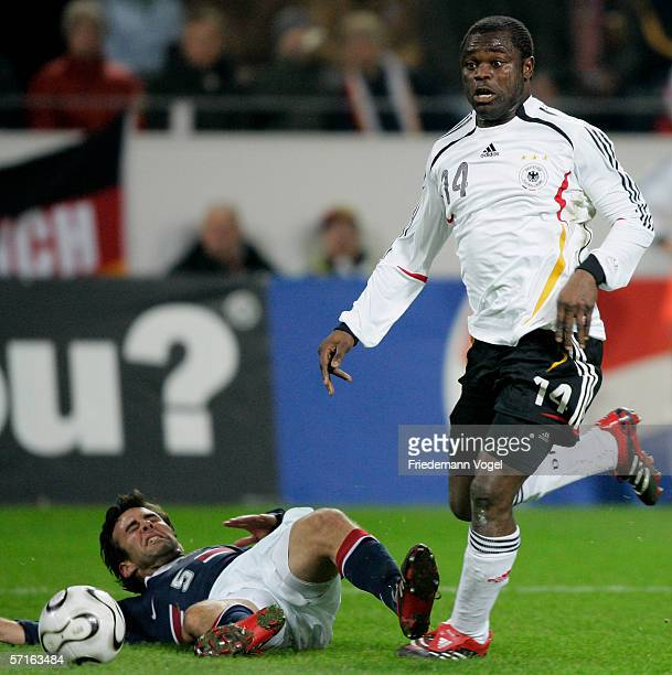Gerald Asamoah of Germany takes the ball past Kerry Zavagnin of the USA during the international friendly match between Germany and the USA at the...