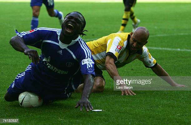 Gerald Asamoah of Schalke falls to the ground during a tangle with Dede of Dortmund during the Bundesliga match between Borussia Dortmund and FC...
