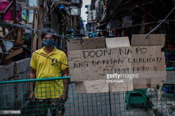 Gerald Bolo poses for a portrait as he guards a makeshift barricade blocking the entrance to Barangay 31 to prevent the spread of COVID-19 in their...