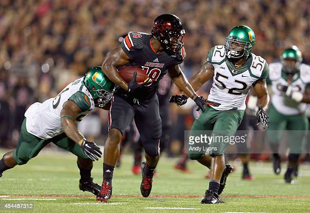 Gerald Christian of the Louisville Cardinals runs with the ball while defended by Raphael Kirby of the Miami Huricanes during the game at Papa John's...