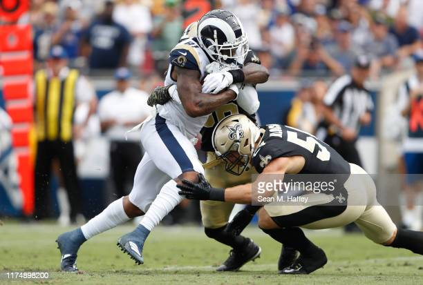 Gerald Everett of the Los Angeles Rams is tackled by Kiko Alonso and Demario Davis of the New Orleans Saints during the second half in the game at...