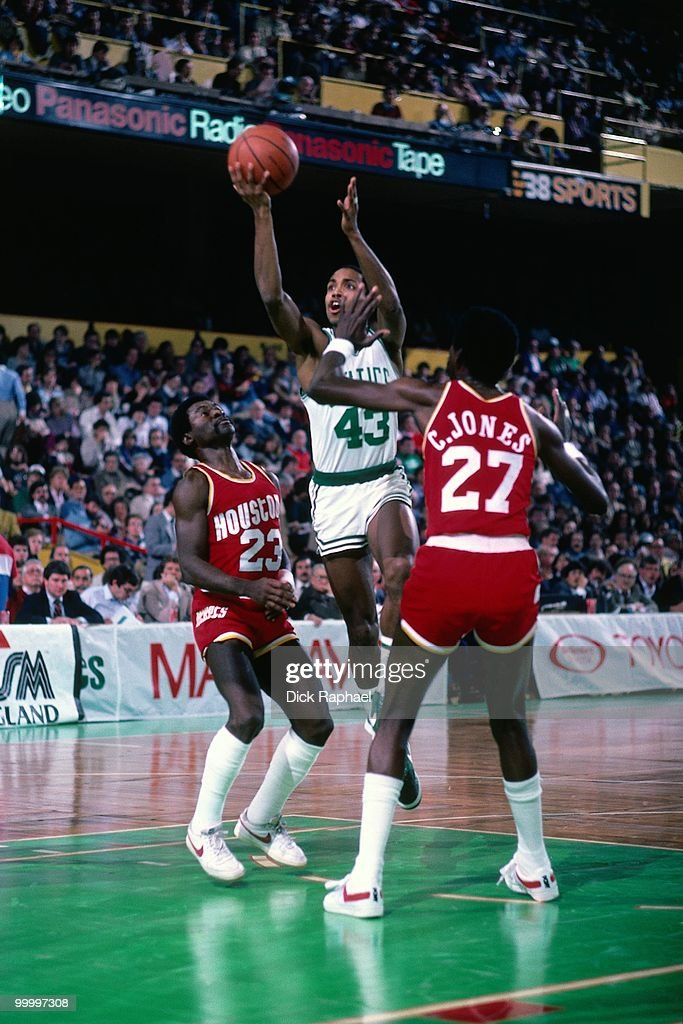 Gerald Henderson #43 of the Boston Celtics shoots a layup against Caldwell Jones #27 and Calvin Murphy #23 of the Houston Rockets during a game played in 1983 at the Boston Garden in Boston, Massachusetts.