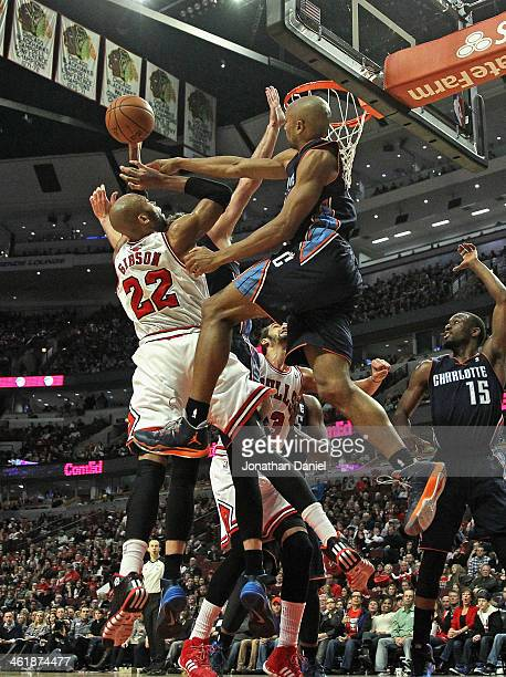Gerald Henderson of the Charlotte Bobcats leaps and fouls Taj Gibson of the Chicago Bulls at the United Center on January 11 2014 in Chicago Illinois...