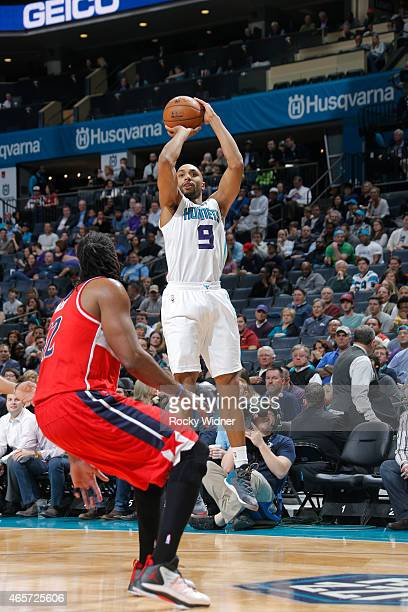Gerald Henderson of the Charlotte Hornets shoots against Nene of the Washington Wizards on March 9 2015 at Time Warner Cable Arena in Charlotte North...