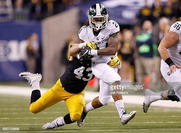 Gerald Holmes of the Michigan State Spartans is dragged down by Josey Jewell of the Iowa Hawkeyes in the Big Ten Championship at Lucas Oil Stadium on...