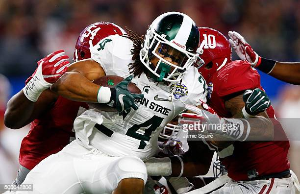 Gerald Holmes of the Michigan State Spartans is tackled by Reuben Foster and Dalvin Tomlinson of the Alabama Crimson Tide in the fourth quarter...