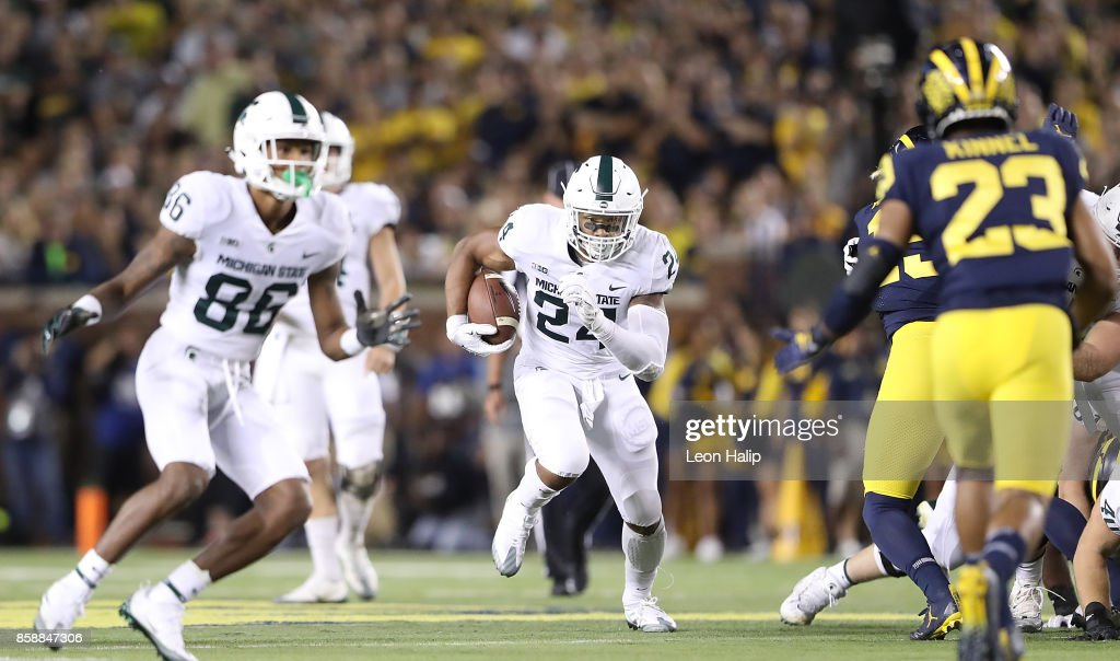 Gerald Holmes #24 of the Michigan State Spartans runs for a first down during the second quarter of the game against the Michigan Wolverines at Michigan Stadium on October 7, 2017 in Ann Arbor, Michigan. Michigan State defeated Michigan 14-10.