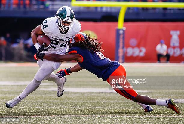 Gerald Holmes of the Michigan State Spartans runs the ball after a catch as Jaylen Dunlap of the Illinois Fighting Illini attempts the tackle at...