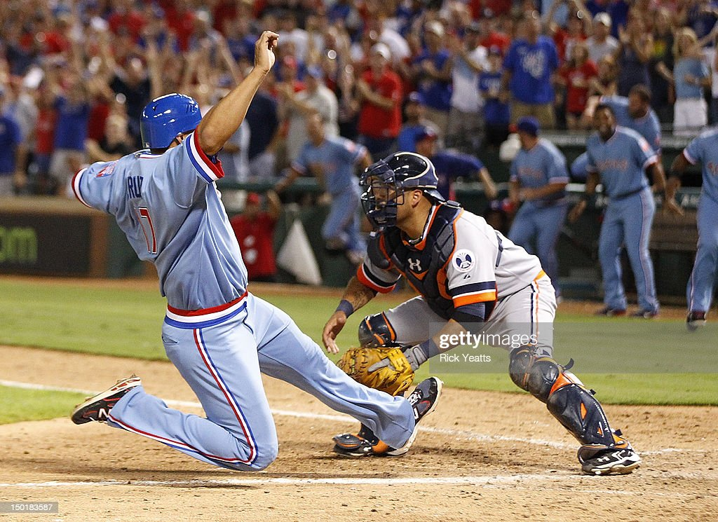 Gerald Laird #9 of the Detroit Tigers looks for the ball as Nelson Cruz #17 of the Texas Rangers scores to win the game on a walk off single by hit by Mike Olt at Rangers Ballpark in Arlington on August 11, 2012 in Arlington, Texas.