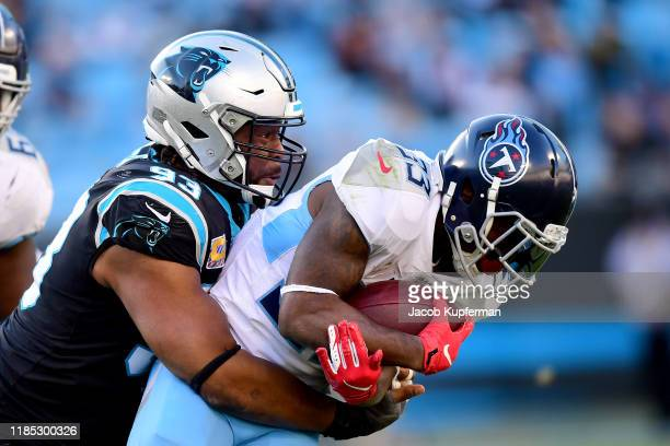 Gerald McCoy of the Carolina Panthers tackles Dion Lewis of the Tennessee Titans in the fourth quarter during their game at Bank of America Stadium...