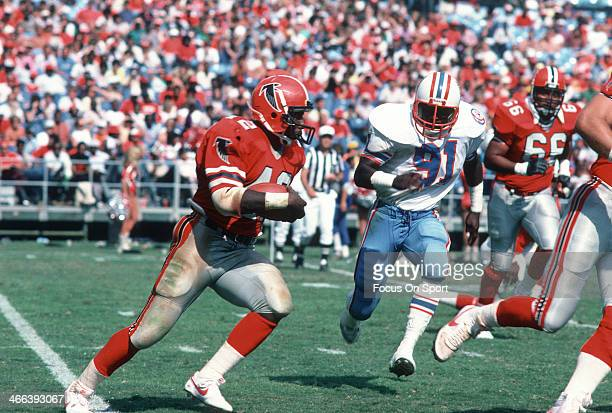 Gerald Riggs of the Atlanta Falcons runs with the ball pursued by Johnny Meads of the Houston Oilers during an NFL football game September 23 1984 at...