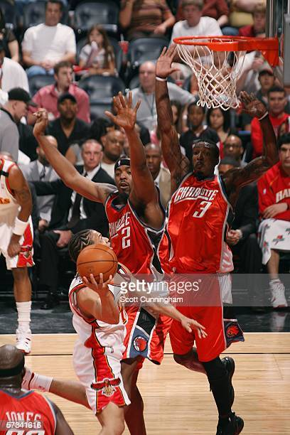 Gerald Wallace and Melvin Ely of the Charlotte Bobcats defend against Tyronn Lue of the Atlanta Hawks on April 14 2006 at Philips Arena in Atlanta...
