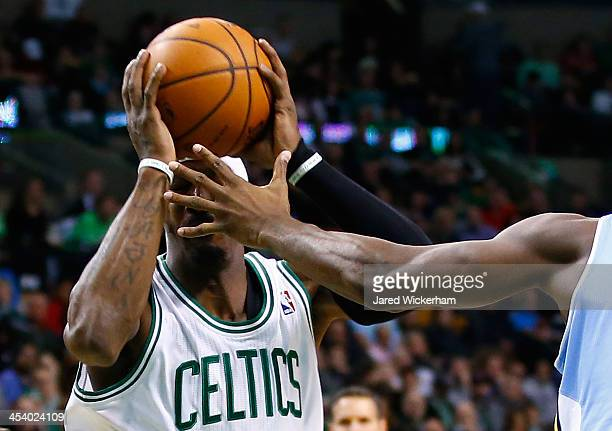 Gerald Wallace of the Boston Celtics is defended by the hand of Kenneth Faried of the Denver Nuggets in the second quarter during the game at TD...