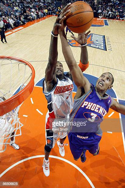 Gerald Wallace of the Charlotte Bobcats attempts to block the shot of Boris Diaw of the Phoenix Suns on December 30 2005 at the Charlotte Bobcats...