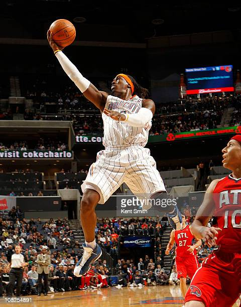 Gerald Wallace of the Charlotte Bobcats skies to the basket against Mike Bibby of the Atlanta Hawks on January 22 2011 at Time Warner Cable Arena in...