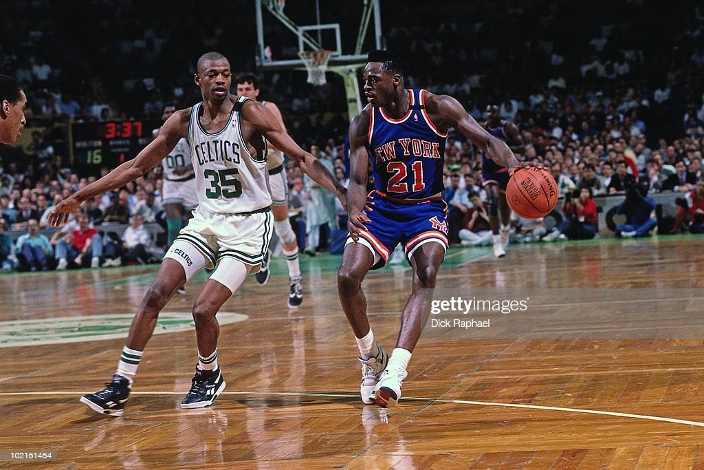 Gerald Wilkins #21 of the New York Knicks drives the ball up court against Reggie Lewis #35 of the Boston Celtics during a game played in 1990 at the Boston Garden in Boston, Massachusetts.