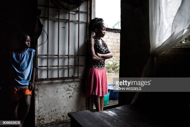 Geraldine 20 years old and who recently lost her cousin Rosette to cholera stands in the door of her family's house waiting for the rain to stop on...