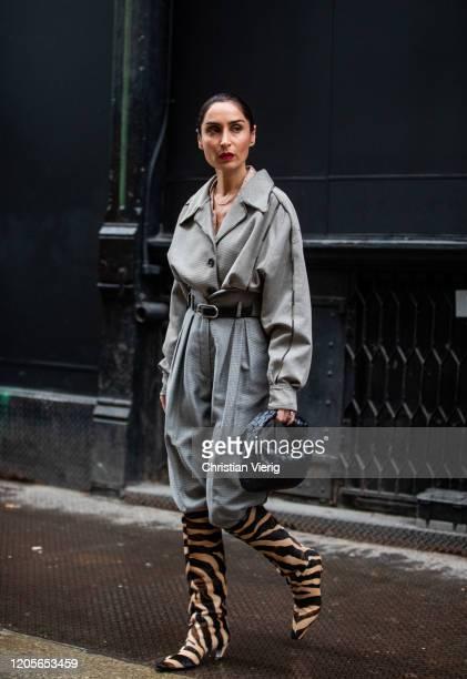 Geraldine Boublil is seen wearing grey high waist pants blazer boots with animal print black Bottega bag during New York Fashion Week Fall / Winter...