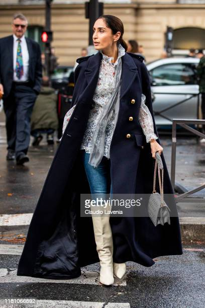 Geraldine Boublil wearing a floral print blouse blue jeans cream boot grey bag and long blue coat is seen outside the Miu Miu show during Paris...