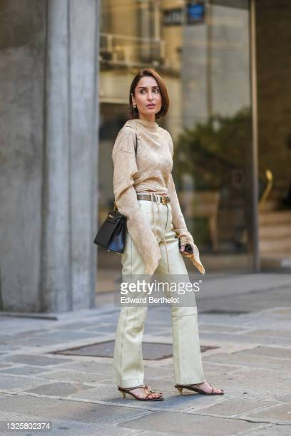 Geraldine Boublil wears a beige linen pullover / top with long oversized sleeves, a brown leather belt, pale green pants, a black leather Hermes...