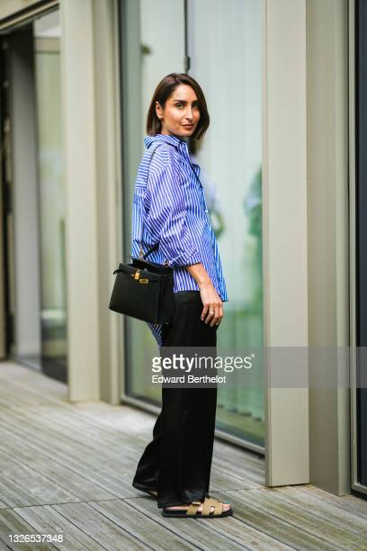 Geraldine Boublil wears a blue and white striped oversized shirt, a black leather Kelly bag, black silky lustrous pants, beige Hermes sandals, during...